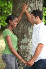 Couple in love stood by tree