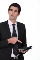 Businessperson pointing at calculator