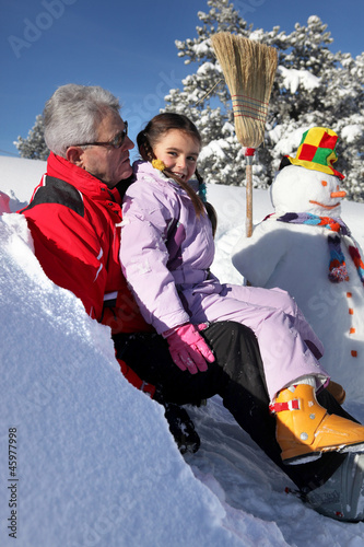 Little girl making a snowman with grandpa