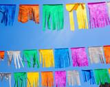 colorful tissue Paper fringe garland under blue sky poster