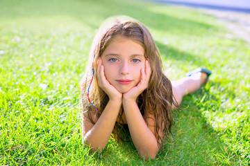 blue eyes children girl relaxed on the garden grass