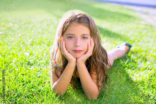 blue eyes children girl relaxed on the garden grass