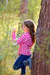 beautiful kid girl profile looking plants in pine forest