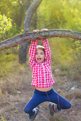children girl swinging in a trunk in pine forest