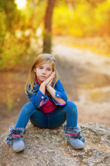 blond kid girl pensive in the forest outdoor sitting