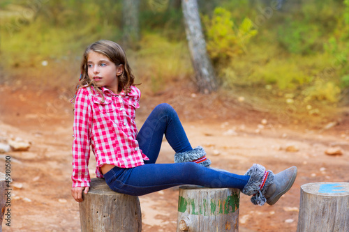children girl relaxed on a tree trunk in the forest