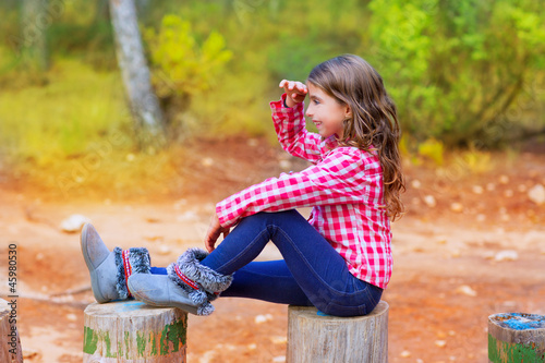 Kid girl sitting in forest trunk looking far away