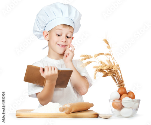 Chef boy is reading a recipe cook