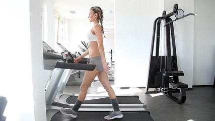 Athletic woman running on the track in gym