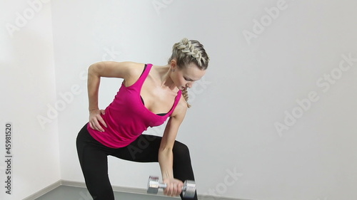 Athletic young woman working with dumbbell isolated on white