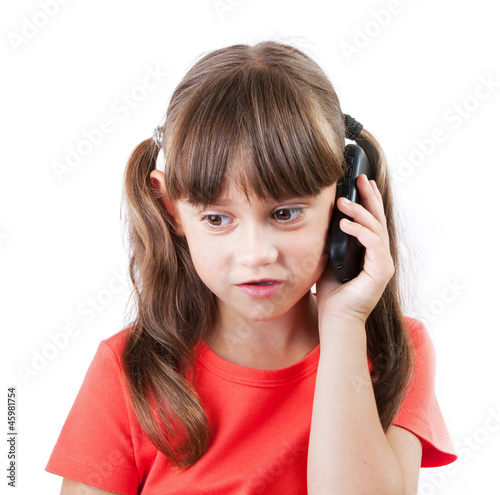 Little girl with a phone on gray background
