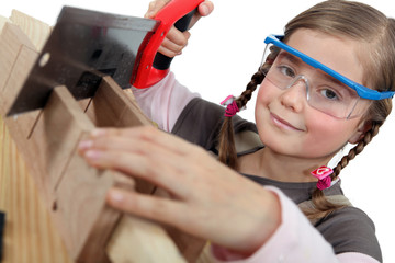 Little girl using a hand saw