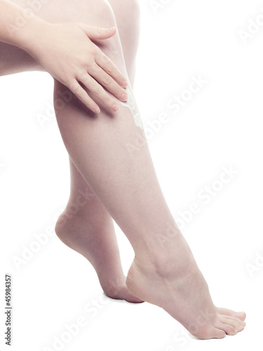 Woman Putting Cream On Her Leg - isolated