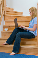 woman with laptop on stairs