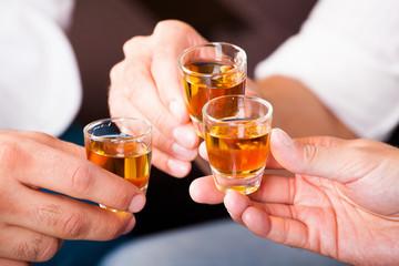 Männer beim Anstoßen mit Rum