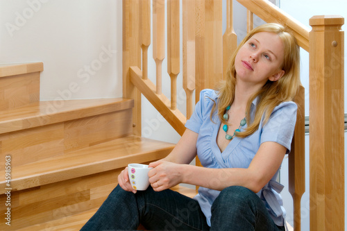 Young woman is sitting on the stairs
