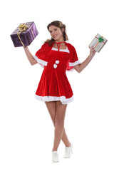 Smiling Miss Santa holding aloft some Christmas gifts