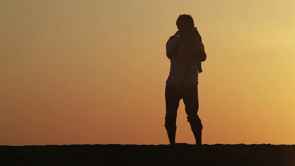 Silhouette of father turns his son over sunset