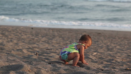 Adorable toddler playing with sand at the beach