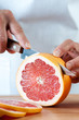Vertical shot of a fresh grapefruit being sliced by female hands