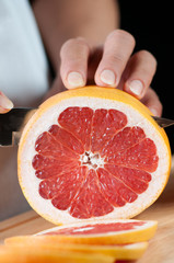 Food preparation – cutting a grapefruit, vertical shot