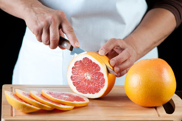 Senior woman cutting grapefruits on a wooden board, studio shot