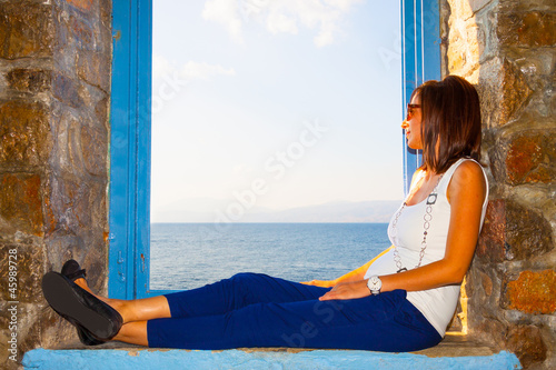 Young beautiful woman posing by window frame