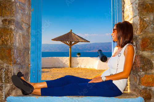 Young woman posing by window by canon view