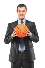 A smiling businessman holding a basketball