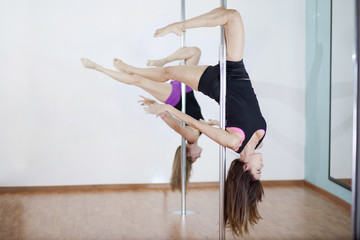 Cute girls showing off during pole fitness class