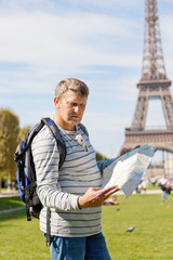 man with a map of the city in hands against the Eiffel Tower