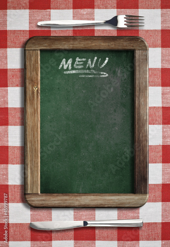 Menu blackboard lying on table with knife and fork