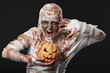 scary mummy waves her arms with pumpkin