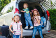 two little girls  and boy standing near the car with backpacks