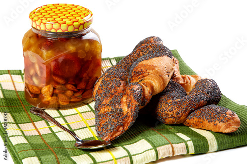 Bank of honey and roll with a poppy on  white background