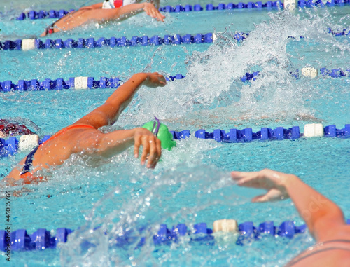 Female swimmers in a close butterfly race at an outdoor pool
