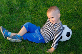 Youngster lying against his soccer ball