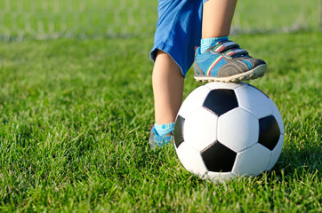 Boy with his foot on a soccer ball