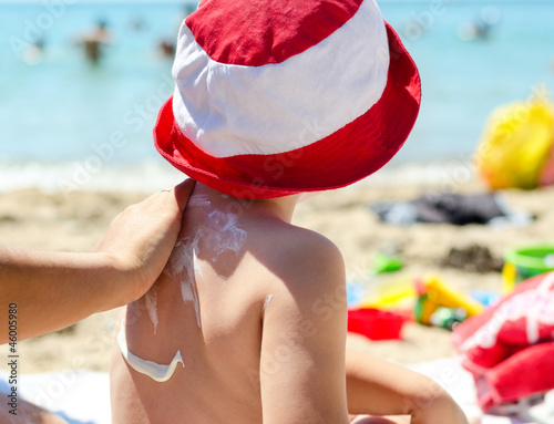 Young boy having sunscreen applied