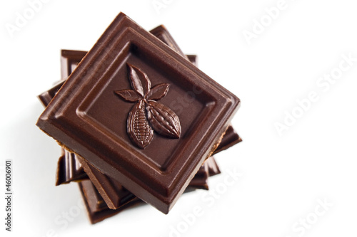 chocolate pieces tower isolated on a white embossed cocoa beans