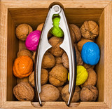 Walnuts in a wooden box with metal nippers poster