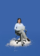 Businesswoman sitting on cloud with computer