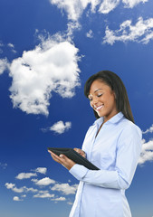 Happy woman with tablet computer and clouds