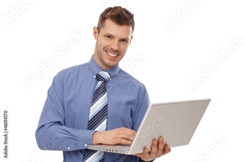Happy businessman holding laptop