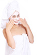 Beautiful woman in towel with facial mask over white background