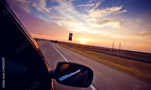 Driving in convertible through highway at sundown