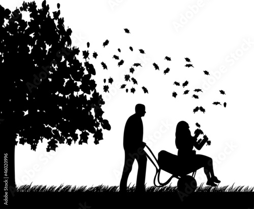 Man pushing a girl in cart in autumn or fall silhouette