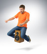 Unreal flying man sitting on a speaker