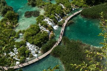 Tourists walk on a path in Plitvice Lakes National Park, Croatia