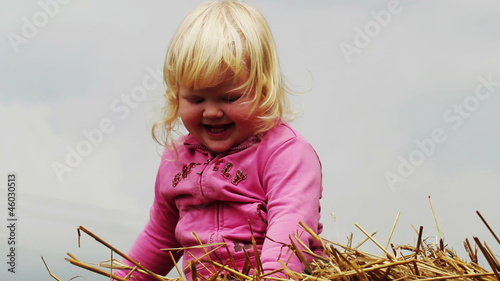 little girl indulges in a haystack